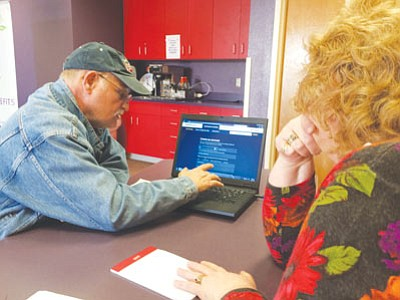 Connie Potter, credit counselor for Kingman Regional Medical Center's patient financial services, helps John Perry sign up for Obamacare during Tuesday's health care enrollment fair at KRMC Professional Medical Building. (HUBBLE RAY SMITH/Miner)