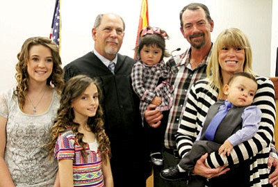 JC AMBERLYN/Miner<BR> From left, the expanded Davis family – Elizabeth, Jazmine, Olivia, 15 months, Walter, Christine and Travis – pose with Superior Court Judge Richard Weiss after Olivia's adoption is complete. Above right, Raymond Cornelia smiles as his adopted daughter, Alyssa, who was added to the family in 2013, pinches his cheeks.