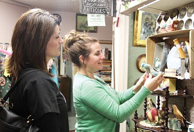 Brenda Arnold, left, of Chandler, and Kingman resident Lisa Ruesch look at collectibles at Kettelhut's Antiques. The women were visiting the store in hopes of finding Fiestaware bowls for Arnold, but purchased a Fiestaware plate instead. (JC AMBERLYN/Miner)