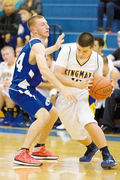 Kingman's Jacob Cave works to get around Kingman Academy's Justice Jackson during Monday's season opener for both squads at KHS. The Academy sped past the Bulldogs, 60-27. (RYAN ABELLA/Miner)