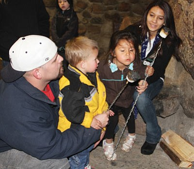 From left to right, Brad and Kade Rhodes, 2, Tru Daniels, 4, and Daisie Kuna were roasting marshmallows Dec 7, 2013. Here, Tru blows on one to cool it. (JC AMBERLYN/Miner)