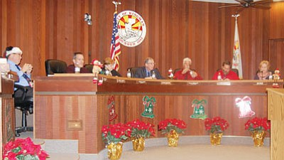 Christmas was in the air at the final City Council meeting of the year Tuesday. Council Chambers was decorated, Vice Mayor Mark Wimpee and Councilman Mark Abram wore nearly matching red shirts and Councilman Larry Carver adorned his head with a Christmas cap.  (DOUG McMURDO/Miner)