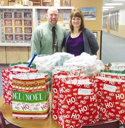 Courtesy<BR> Cerbat Elementary School Principal Tony Victory and Assistant Principal Vicki Trujillo display some of about 15 bags filled with Christmas presents that were brought in by Kingman Presbyterian Church for students at the school.