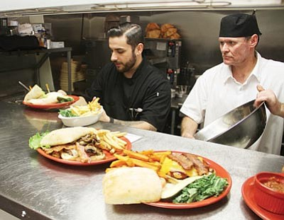 The Canyon 66 Restaurant will be among the establishments that are open this Christmas. Here, Josh Higgs, executive chef (left) and Don Hunt, sous chef, work on Saturday. (JC AMBERLYN/Miner)