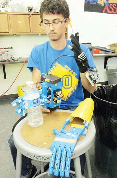 KIM STEELE/Miner<BR>  Jesse Marquez, 17, a senior at Kingman High School, demonstrates how he uses his gloved hand to tell a robotic hand he created to pick up and hold a bottle of water.