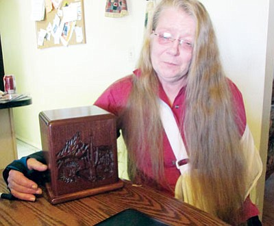 """KIM STEELE/Miner<BR> Victoria Borland, her eyes red and puffy from crying, hugs the ashes of her late husband, Robert """"Bob"""" Borland. """"After he died, I found myself getting up at night to get his medication for him and realized he wasn't there,"""" she said. """"I would go back to bed and take his ashes and sleep next to them. I miss him so much."""""""