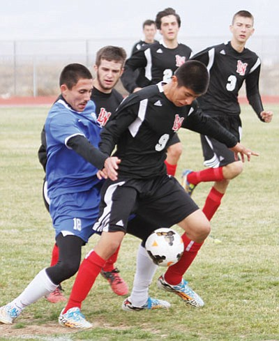 Lee Williams' Justin Sturgill (9) fights for control of the ball against Kingman Dec. 12. Sturgill scored the Vols' two goals in their win over MALC Tuesday in Bullhead City. (JC AMBERLYN/Miner)