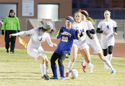 Kingman's Brooklyn Ness (1), Catherine Angle (14), Megan Gaul, and Alyssa McBride (4) join forces to get the ball away from Prescott's Mikayla Sell Wednesday at KHS. Sell had a hat trick with three goals for the Bears in their win over Kingman, 5-0. (RYAN ABELLA/Miner)