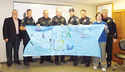 Courtesy<BR> Canyon Community Church recently provided the Kingman Police Department with a banner thanking them for the job they do. From the left is Pastor Kent Simmons, Sgt. Evan Kunert, Chief Bob DeVries, Officer Denny Gaddis, Officer Gabriel Brown, Officer Dennis Farrington, Erin Cochran and Deputy Chief Rusty Cooper.