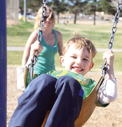 JC AMBERLYN/Miner<BR> Gabriel Thompson, 3, gets a push on a swing from his mom, Terra, Friday during sunny weather in Centennial Park.