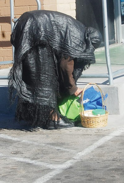 A homeless woman tends to her precious belongings Tuesday afternoon in downtown Kingman. (DOUG McMURDO/Miner)
