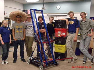 From left, Team 60 Robotics Club members Rebecca Legget, Jesse Marquez, John Lewis, Alex Schnieder, Jesse Masters, Eric Venenga and Luke Pierson display this year's robot their group created for the FIRST Robotics Competition regionals that will take place in Chandler and Las Vegas.  (Courtesy)