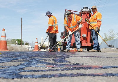 Left to right are Joe Wyatt, Tom Blum and Melvin Dubay putting on a seal coat to fill in cracks and protect the road from water damage.