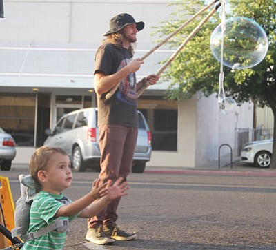 Travis Brox makes giant bubbles to the delight of 2-year-old Caleb Sheldon during the KABAM! Poetry Slam Friday evening. (JC AMBERLYN/Miner)
