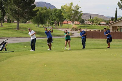 The Kingman Academy High golf team gets some chipping practice in Tuesday at Cerbat Cliffs Golf Course with the Division III state championship ahead of them on Friday at Antelope Hills Golf Course in Prescott Valley. From left to right are Caleb Boyett, Tristen Pitts, Haley Muswick, Raphael Choi and Mattew Suh. (SHAWN BYRNE/Miner)