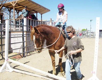 Becky Radimaker holds tightly to the reigns as she rides Elvis over an obstacle that will be part of the trail class during the horse show. Elvis is being guided by volunteer Cindy Crawford.