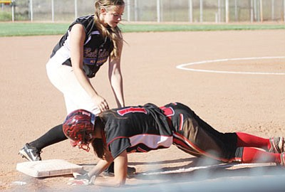 Lee Williams' Cassie Finkbeiner dives back safely to third base as Kingman's Catherine Angle applies a tag April 28. The LWHS softball team led an outstanding athletic year for the Volunteers, reaching the second round of the Division III state tournament. (JC AMBERLYN/Miner)