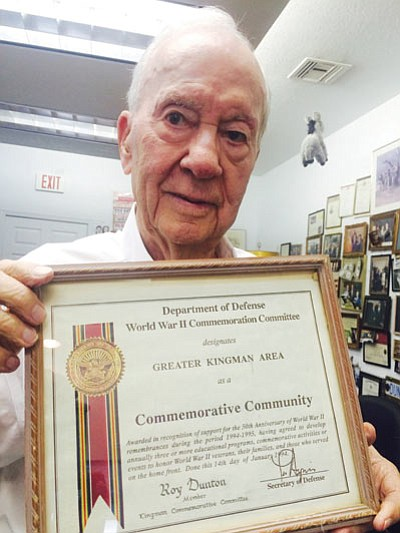 Roy Dunton, 93, shows a World War II Commemorative Community plaque from the Department of Defense inside his office at Dunton Motors. (HUBBLE RAY SMITH/Miner)