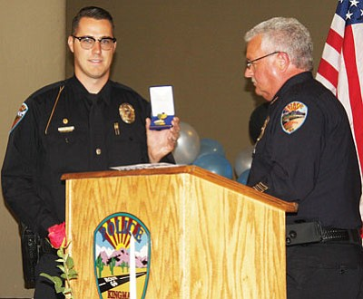 Courtesy<BR>Police Chief Bob DeVries presents the Distinguished Service Award to officer Chaz Truver.