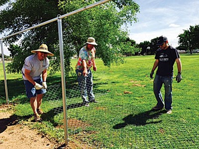 Volunteers put in fencing around a community garden in Kingman's Cecil Davis Park. (Courtesy)