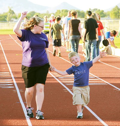 JC AMBERLYN/Miner<BR> Gavin Harmon, then 3, and his mother Tanya enjoy walking a lap with other family members during the Relay for Life in June 2012. Their family was there for many of their relatives who have been affected by cancer.