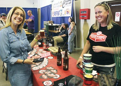 Robin Poole, left, accepts a beer sample from Stacy Thomson, owner of the local House of Hops, during the 3rd annual Beer Fest Saturday at the Mohave County Fairgrounds. There were 13 vendors from around the state, offering over 100 beers for sampling and sale. Over 400 people were expected at the event, which was staffed by volunteers. and organized by DMS Events. (JC AMBERLYN/Miner)