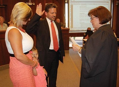 DOUG McMURDO/Miner<br>Magistrate Kathy McCoy administers the oath of office to her replacement, Jeffrey Singer, at Tuesday's City Council meeting. With Singer is his wife, Brandy, and daughter Maddie. McCoy is set to retire after 29 years on June 30.