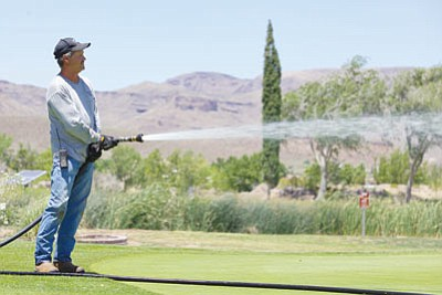 Thomas Pachardo waters the putting green at Cerbat Cliffs Golf Course Wednesday. Pachardo's light colored, long-sleeved shirt fits what OSHA recommends in terms of clothing while working in the heat. (RYAN ABELLA/Miner)