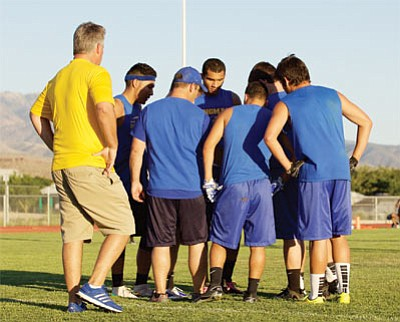 Led by head coach Greg Tonjes (wearing yellow), the Kingman Bulldogs huddle up during the 7-on-7 passing league competition Tuesday at Lee Williams. (RYAN ABELLA/Miner)