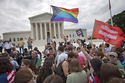 The crowd reacts as the ruling on same-sex marriage was announced outside of the Supreme Court in Washington on Friday. The Supreme Court declared Friday that same-sex couples have a right to marry anywhere in the US. (AP Photo/Jacquelyn Martin)