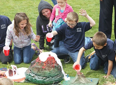 "Desert Willow Elementary School held its annual volcano science project in May. Third grade students make ""volcanoes"" using ingredients from a list of materials and then made them ""erupt"" at the school playground. Here, from left to right, Logann Fossum, 9, Kari, Hayli, 4, and Byron Murphy, 9, and Jaren Rucker, 8, react as volcanoes foam over. (JC AMBERLYN/Miner)"