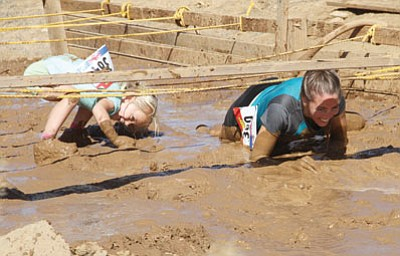Rachel Damron and her daughter, Samantha, 5, crawl through the mud during the final part of the course Saturday.
