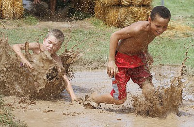 James Wilson, 9 (left), and Keygun Field, 8, race in the mud at last year's Mud Mania. (JC AMBERLYN/Miner)