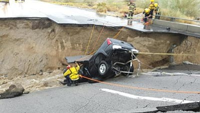 In this photo provided by the CAL FIRE/Riverside County Fire Department, emergency crews respond after a pickup truck crashed into the collapse of an elevated section of Interstate 10 Sunday in Desert Center, Calif.  The bridge, which carries the eastbound interstate about 15 feet above a normally dry wash, snapped and ended up in the flooding water below, the California Highway Patrol said, blocking all traffic headed toward Arizona.