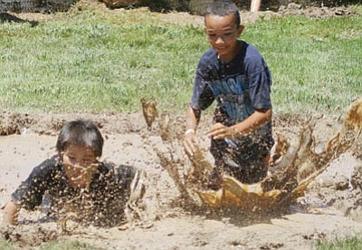 Isaac Cotera, 9, and Jordan Williams, 8, compete in the 37th Annual Mighty Mud Mania at Firefighter's Park July 16.