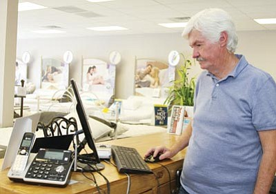 "Jerry Boyd, Owner of Boyd's Outlaw Sleep Center, stands by his computer at the store Tuesday. Someone tried to run what's known as the ""Nigerian"" scam on the business. (JC AMBERLYN/Miner)"