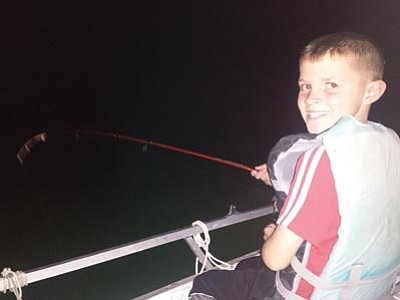 Jacob Parrott, 9, from Kingman is all smiles as he reels in another Lake Mead striper. Jacob was fishing with his father Adam and grandfather Dan. (DON MARTIN/For the Miner)