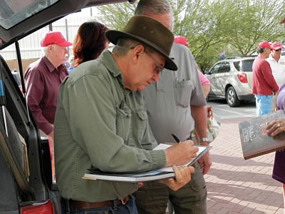"Author Jim Hinckley signs copies of ""Ghost Towns of Route 66"" after talking about the highway's colorful history with a tour group from Australia. (Courtesy)"