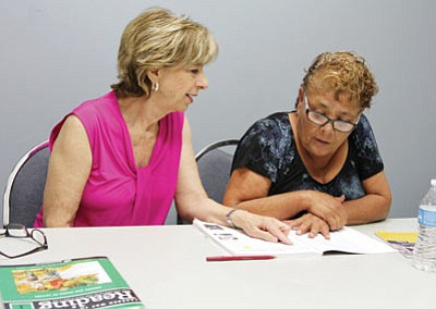 Gail Salmon (left) tutors Carolina Campost Friday at the Kingman Library. (JC AMBERLYN/Miner)