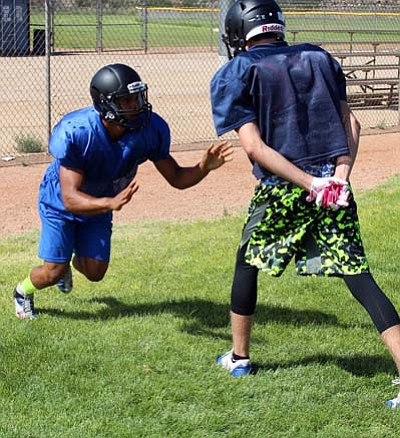 SHAWN BYRNE/Miner<BR> Kingman Academy's Jordan McDowell-Seybert gets off the line against Andrew Quick, right, during a defensive end drill Saturday at Southside Park.