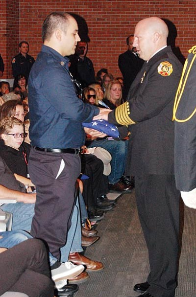DOUG McMURDO/Miner<BR> Kingman Fire Chief Jake Rhoades, right, presents the flag to firefighter Marc Johnston at the memorial service for Johnston's father, Bill, a 33-year KFD veteran who died Aug. 1. Rhoades said Johnston was constantly giving of himself, both in his professional and personal lives.