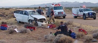 Golden Valley firefighters Morgan Rosencrans, standing by the car, and Chad Lewis tend to two of four teenagers who were injured in a single-vehicle crash Tuesday evening as they await a third ambulance, in the background, to arrive. The driver of the vehicle was deliberately causing the car to fishtail on a dirt road prior the crash, according to the Mohave County Sheriff's Office. (GVFD/Courtesy)