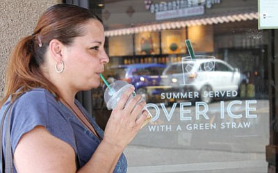 Jackie Carrasco tries to stay cool with a cold drink outside of Starbucks on Stockton Hill Road Tuesday. (JC AMBERLYN/Miner)
