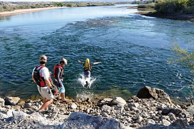 "A Mohave County Sheriff's Office Search and Rescue member uses the classic ""belly flop"" technique to enter the Colorado River during swift water rescue training at Big Bend on the Nevada side of the Colorado River. The technique helps rescuers avoid hitting their heads on obstructions that may be below the surface, such as a rock or tree branch. (BUTCH MERIWETHER/Courtesy)"