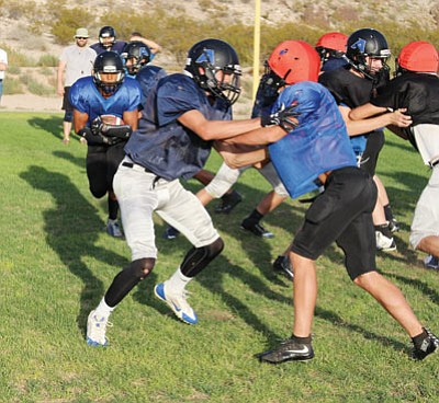 Academy's Jordan McDowell-Seybert rushes up the middle during Wednesday's practice at Southside Park. The Tigers visit Tonopah Valley tonight. (SHAWN BYRNE/Miner)