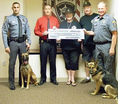 Eva and Gary Corbett of Friends of Mohave County K9 Unit coordinated a 50/50 drawing that raised $1,200 for the county's four-legged law enforcement officers. From the left are Sgt. Raja Karim and K9 Ecko, Capt. Dean McKie, Eva Corbett and Chuck Ferris of Friends of Mohave County K9 Unit, and deputy Kerry Schanaman with K9 Xena. The unit is funded solely through donations. (Courtesy)