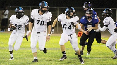 Estrella's Joe Logan (22) follows his offensive line as the Tigers' Matt Timmerman pursues Friday at Southside Park. Logan ran for five first-half touchdowns in Estrella's 56-7 win over the Academy. (ALAN CHOATE/Miner)