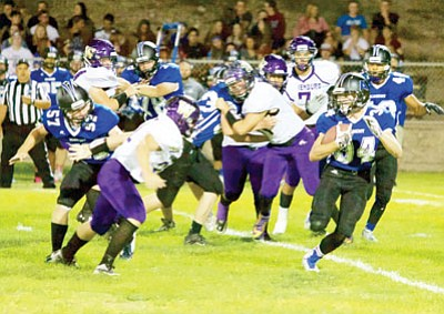 RYAN ABELLA/Miner<BR> Kingman Academy's Clayton Holloway looks to run around Wickenburg's defense during the Tigers' 49-20 Homecoming loss Friday at Southside Park. Holloway rushed for 103 yards and returned a kickoff 80 yards for a touchdown.