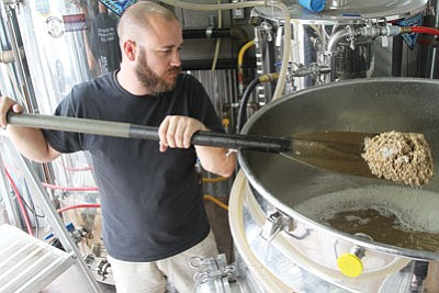 Tim Schritter stirs a vat of beer in downtown Kingman. (JC AMBERLYN/Miner)