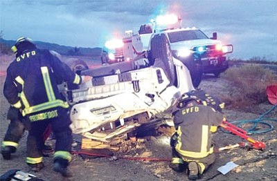 A woman's arm can be seen on the ground under her car while Golden Valley firefighters work to extricate her early Tuesday morning. The woman sustained moderate to severe injuries after rolling several times. (Courtesy)